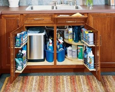 small trashcan under sink (maybe even small compost pail), with curving side shelves, bathroom cleaning products in bucket for easy transfer, storage shelf on inside cabinet doors