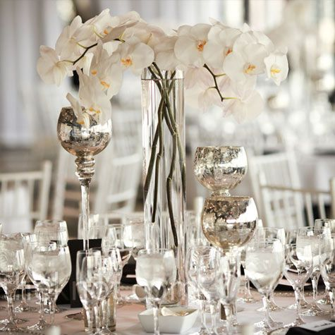 Modern Orchid Centerpieces      Globe mercury glass candle-holders surrounded the modern orchid arrangements to create a romantic vibe.