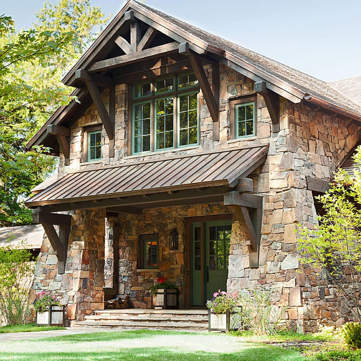 lovely stone and timber homes #6: A copper shed roof shields the front porch of the stone-and-timber house