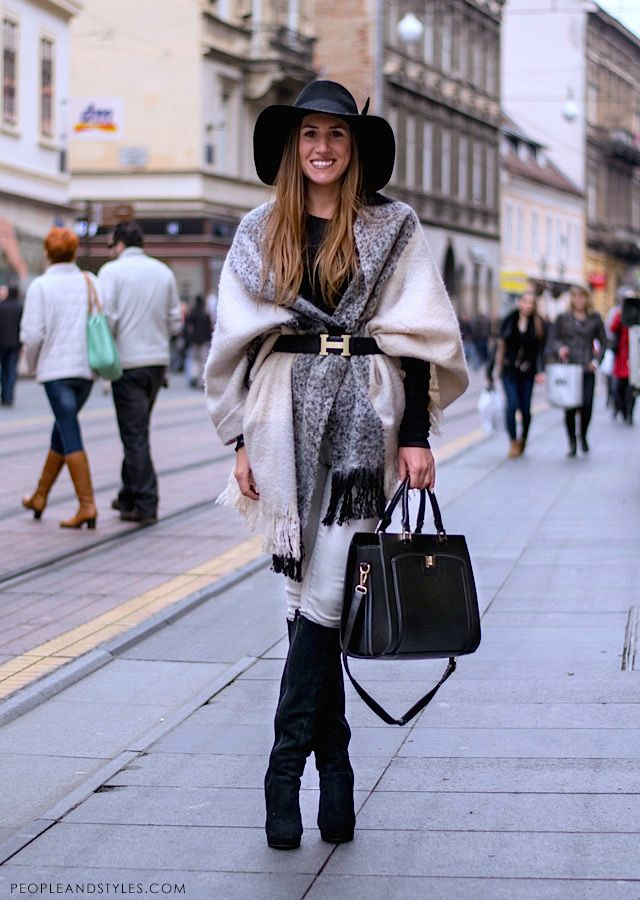 Floppy hat, Hermès belt, black bag, knee high black boots, shawl/cape. Great street style look.