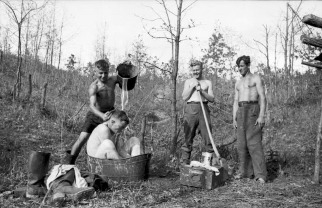 1943 - Rußland, bei Orel (?).- Soldaten mit freiem Oberkörper in Wäldchen, Soldat in Wanne beim Baden, Kamerad Wasser aus Eimer gießend