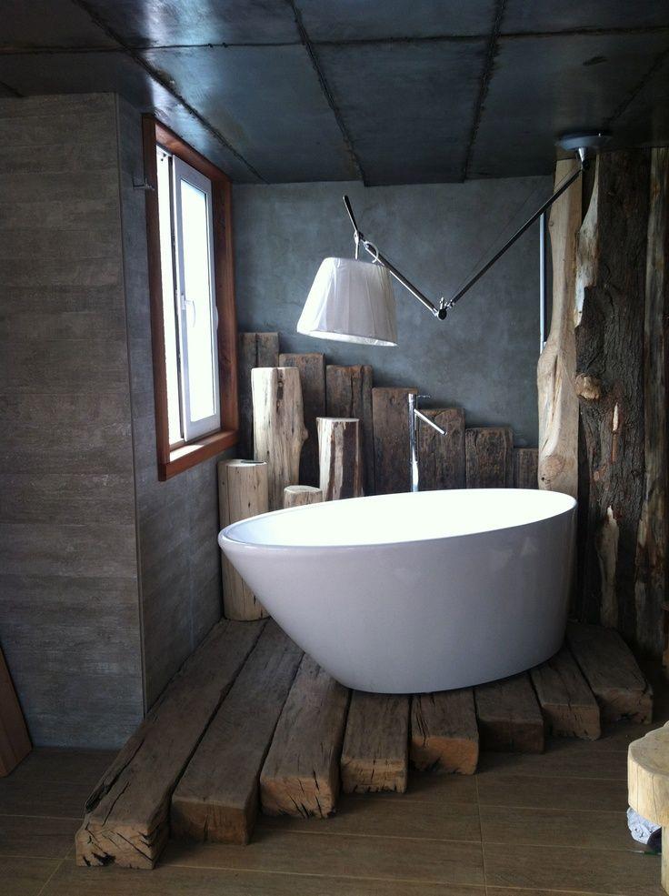 Kleine moderne Badewanne in der Wohnnische mit Holzdielen