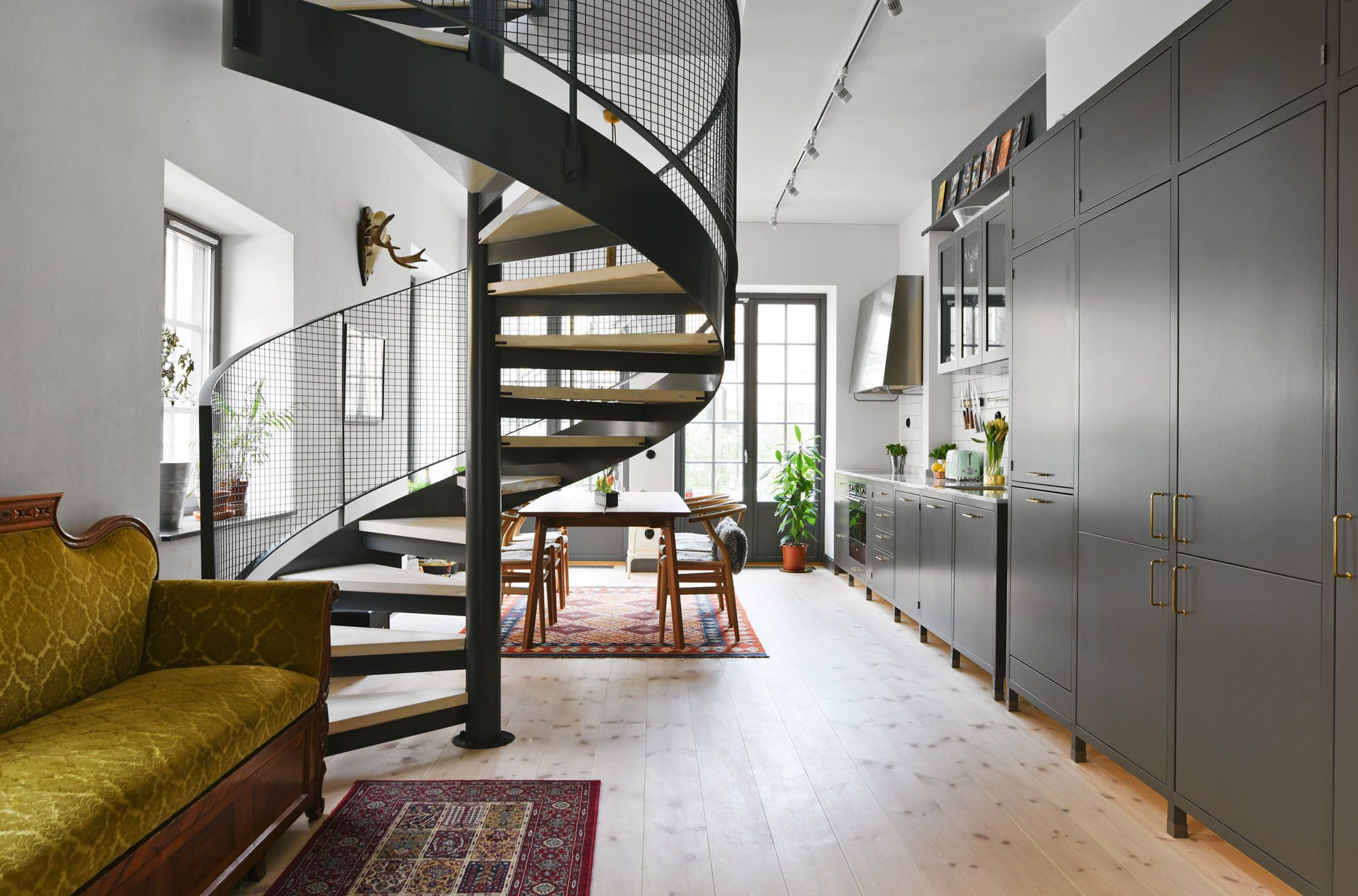 Main room is divided by a metal and wood spiral staircase in this townhouse located in Stockholm. [2000  1320]