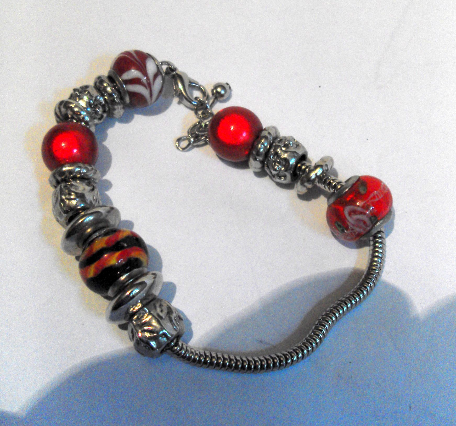 B11242 £15 inc UK Post. Offers welcome. Contemporary multi type (primarily red tones) metal and glass bead bracelet on silver tone snake link chain with claw catch. The bracelet and catch are structurally sound. The bracelet measures approximately 9in long, including catch and extension. Weighs about 29g.