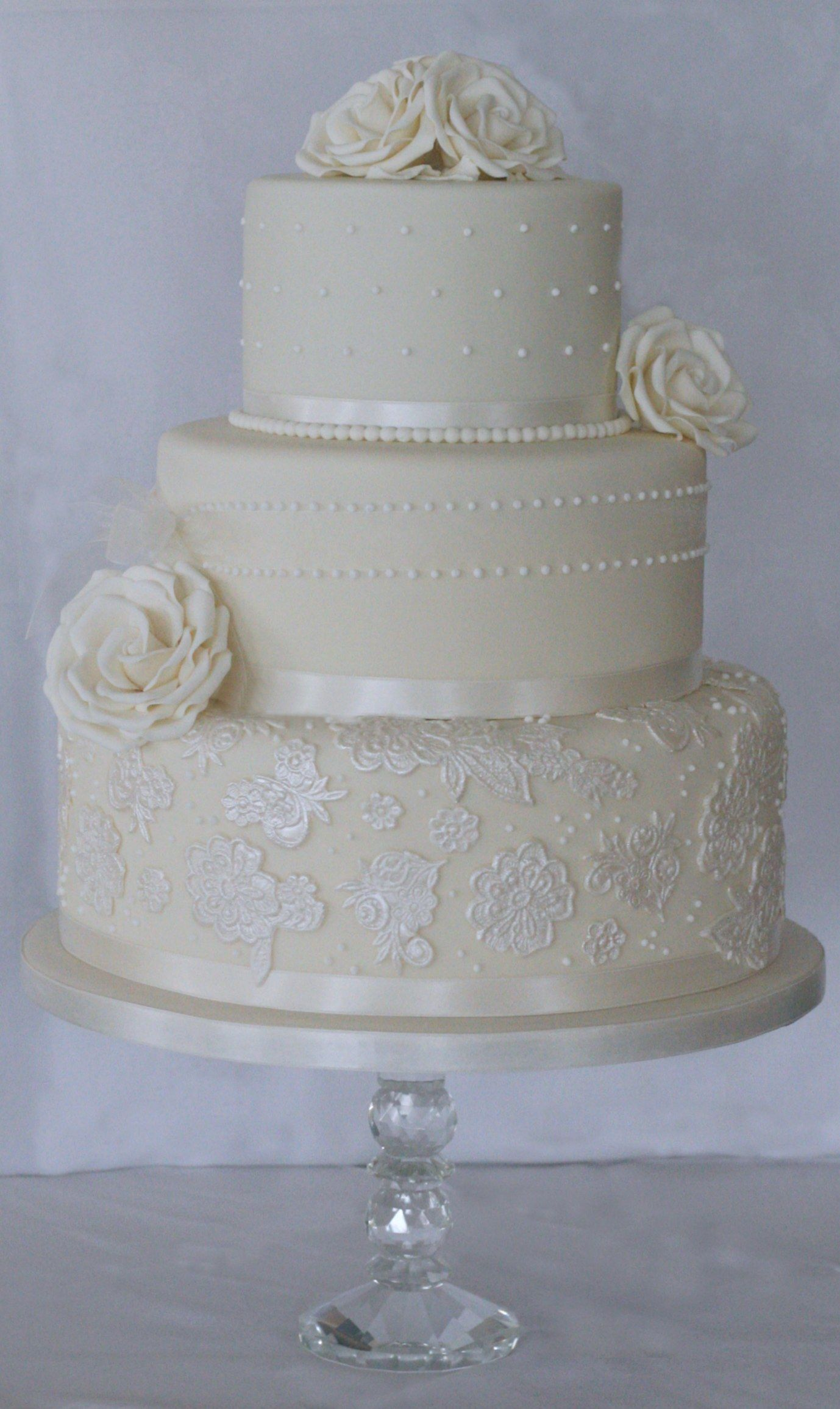 3 Tier Ivory Wedding Cake Finished With Beautiful Handcrafted Sugar Roses,  Royal Iced Swiss Dots And Lustred Sugar Lace To Finish The Look .