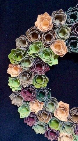 12 round paper rosette wreath. Rosettes made from coordinating cardstock for durability. Each rosette is approx 1. Mounted on foam core board.
