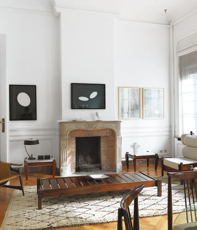 """The drawing room, the couple's principal entertaining space, contains many highlights of the exhibition, including two Tonico lounge chairs by Sergio Rodrigues; a jacaranda bench by Alberto Reis; a leather-and-rosewood sling chair fabricated by Liceu de Artes e Oficios de São Paulo; and drawings by the contemporary Brazilian artist Paulo Climachauska. """"Furniture is more beautiful with a patina—and this comes from years of careful and loving use."""" —Kathryn Smith  Photo by Chris Tubbs."""
