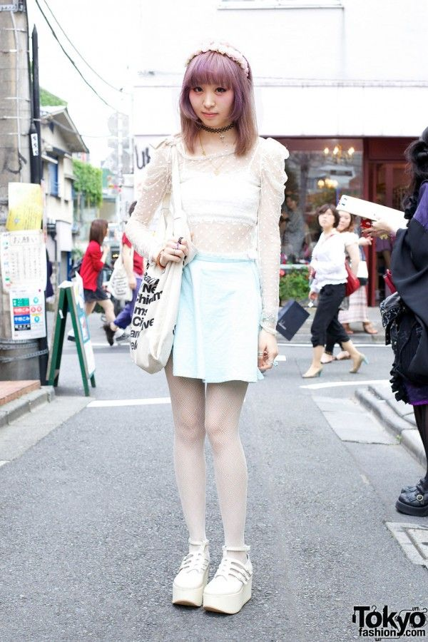 19-year-old student wearing a cute flower headband, sheer top, blue skirt, and Tokyo Bopper platform shoes on the street in Harajuku.
