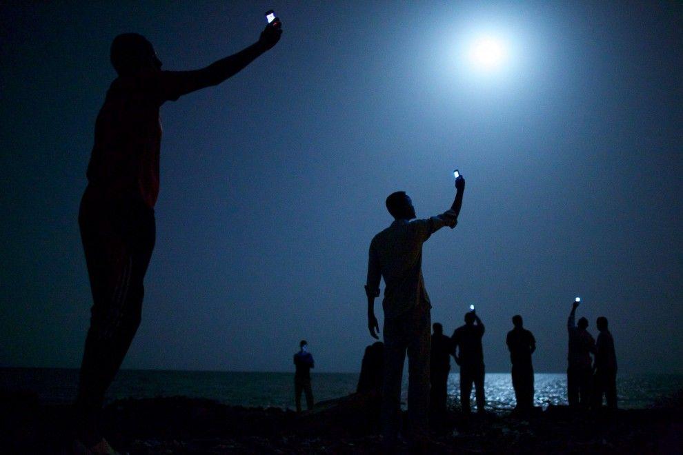 La fotografia 'Signal' di John Stanmeyer della VII Photo Agency ha vinto il World Press Photo of the Year 2013. Nell'immagine scattata lungo la costa di Gibuti alcuni migranti africani alzano al cielo i loro telefoni celullari per catturare il segnale dalla vicina Somalia e contattare i parenti lontani