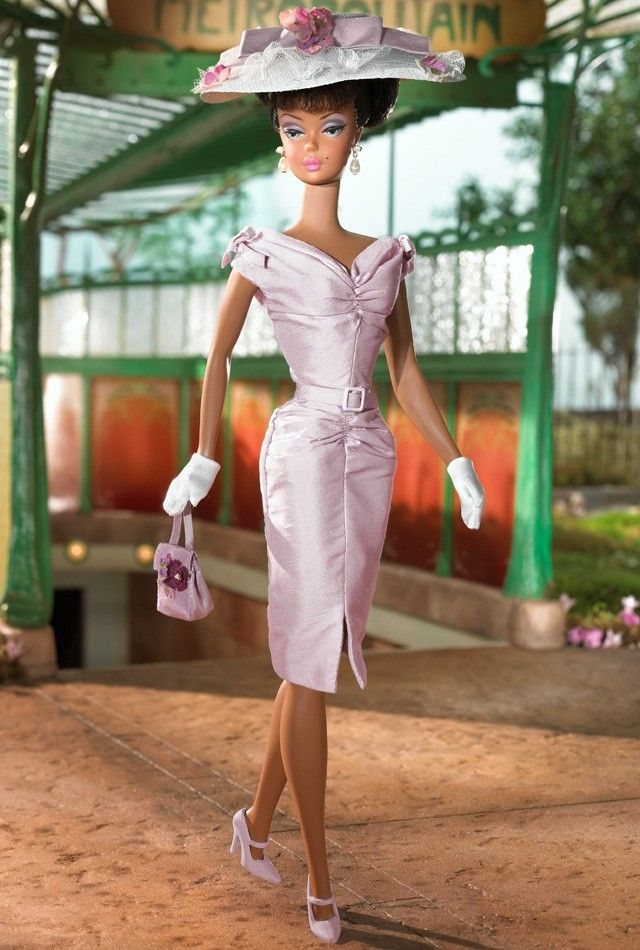 Sunday Best™ Barbie® Doll  The second African-American doll in the Barbie® Fashion Model Collection, Barbie® doll looks lovely in a lilac shantung sheath dress. Her dress is accented with a slit at the front, small bows at the shoulders, and self-belt. Her accessories include a white straw cloth hat with white tulle, lilac shantung bow, and lilac flowers. She also has short white gloves, faux pearl drop earrings, and lilac heels.