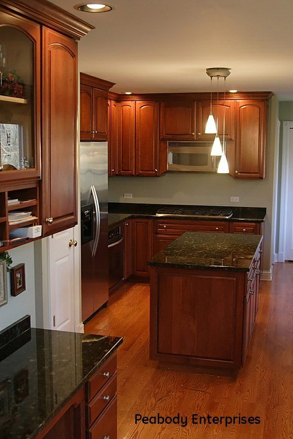 cherry wood cabinets with black counters and appliances | Kitchen ...