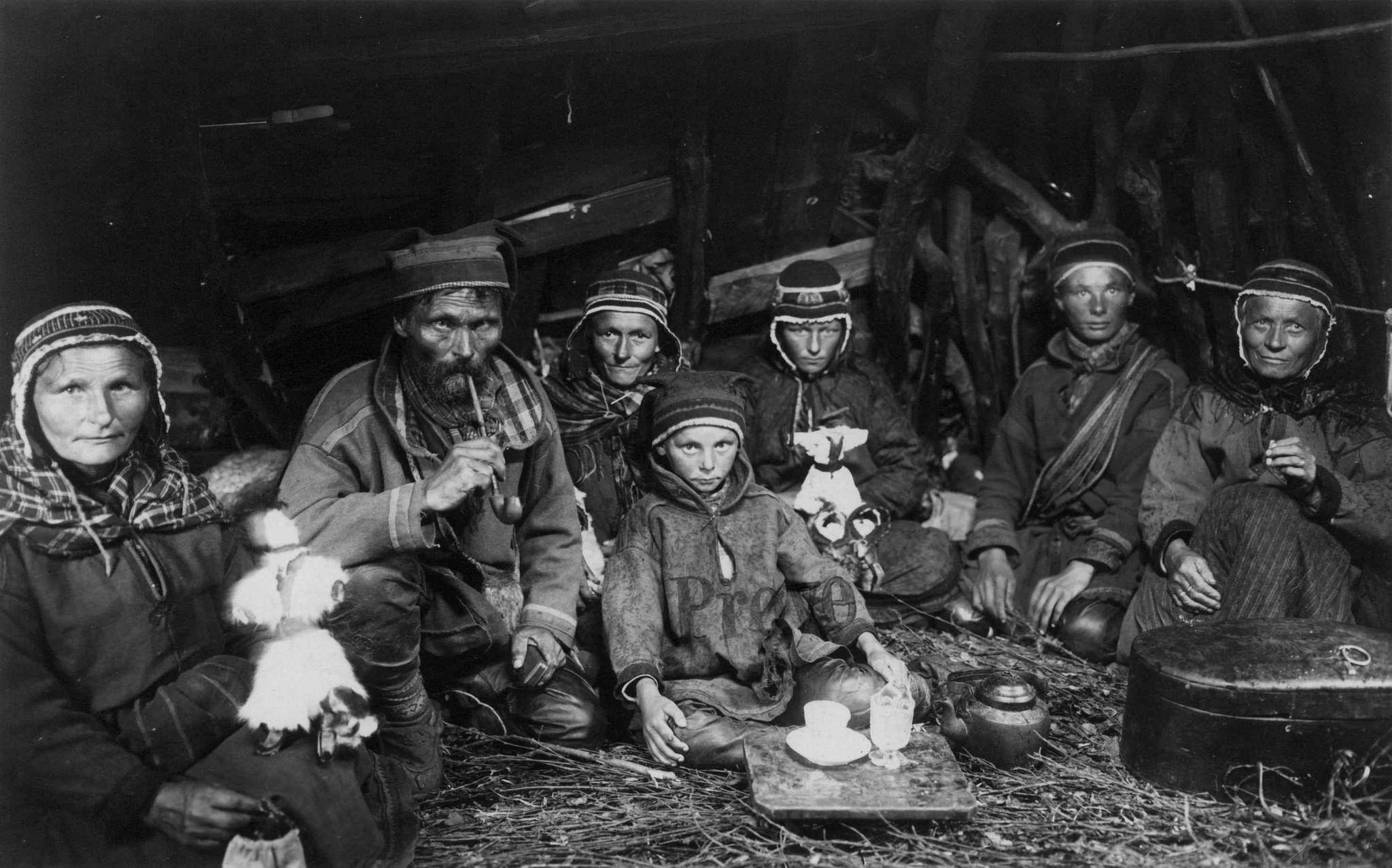 Svenske samer sitter samlet i en gamme på gulvet ved et lite kaffebord med en kaffekopp og en fløtemugge på, ved siden av står kaffekjelen. Nord-Norge 1907.