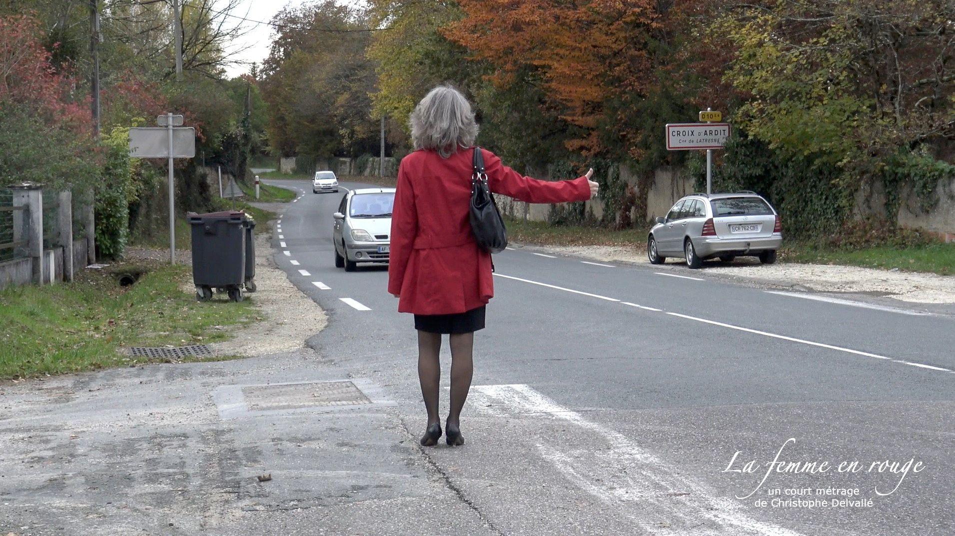 Stoppeuse. Femme faisant du stop sur une route de campagne, vue de dos avec un trench rouge et une jupe noire.