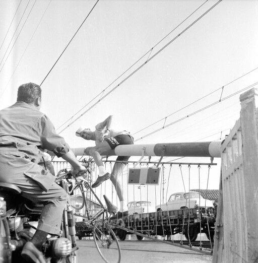 Au Tour 1961, Emmanuel Busto bloqué sur une barrière de passage à niveau qui se relevait..