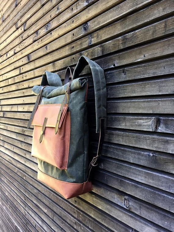 NEW VERSION of this classic Treesizeverse design This backpack is made with olive green gride waxed canvas with an outside pocket made in oiled leather.(color of the leather is cognac) I made it into an everyday backpack/rucksack, with padded heavy weight waxed canvas shoulder straps. Roll to close top, and outside pocket with protective flap made in oiled leather. The bottom of this bag is also made in oiled leather.. The bag closes with roll to close system and snaps with a waxed le...