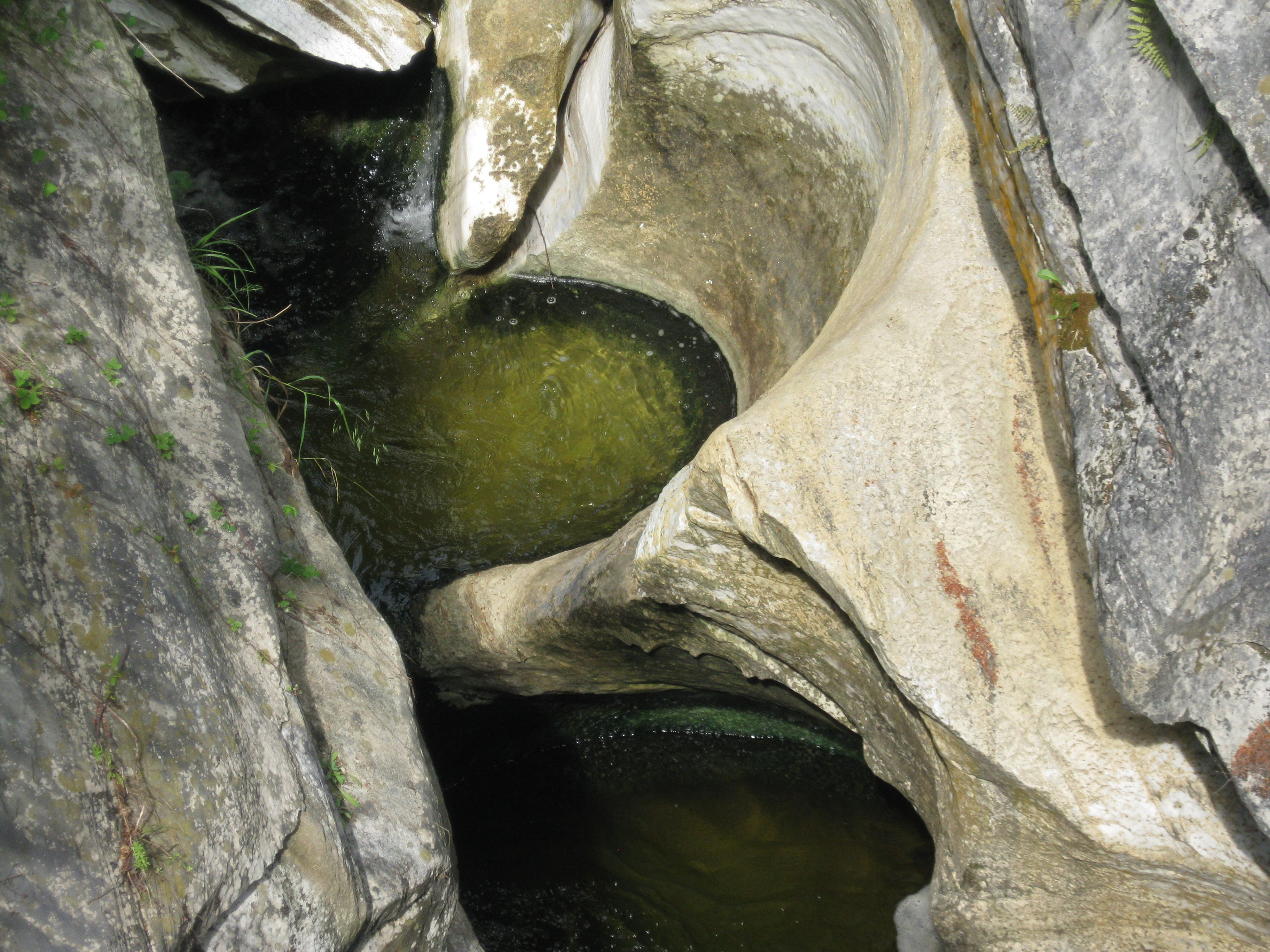 """Glacial potholes. The 'potholes' found in the chasm are products of a process called """"rock drilling"""". Stones, or cobbles, are caught in the current and are bounced by the rushing water. The cobbles nick away at the bedrock creating deep circular holes."""
