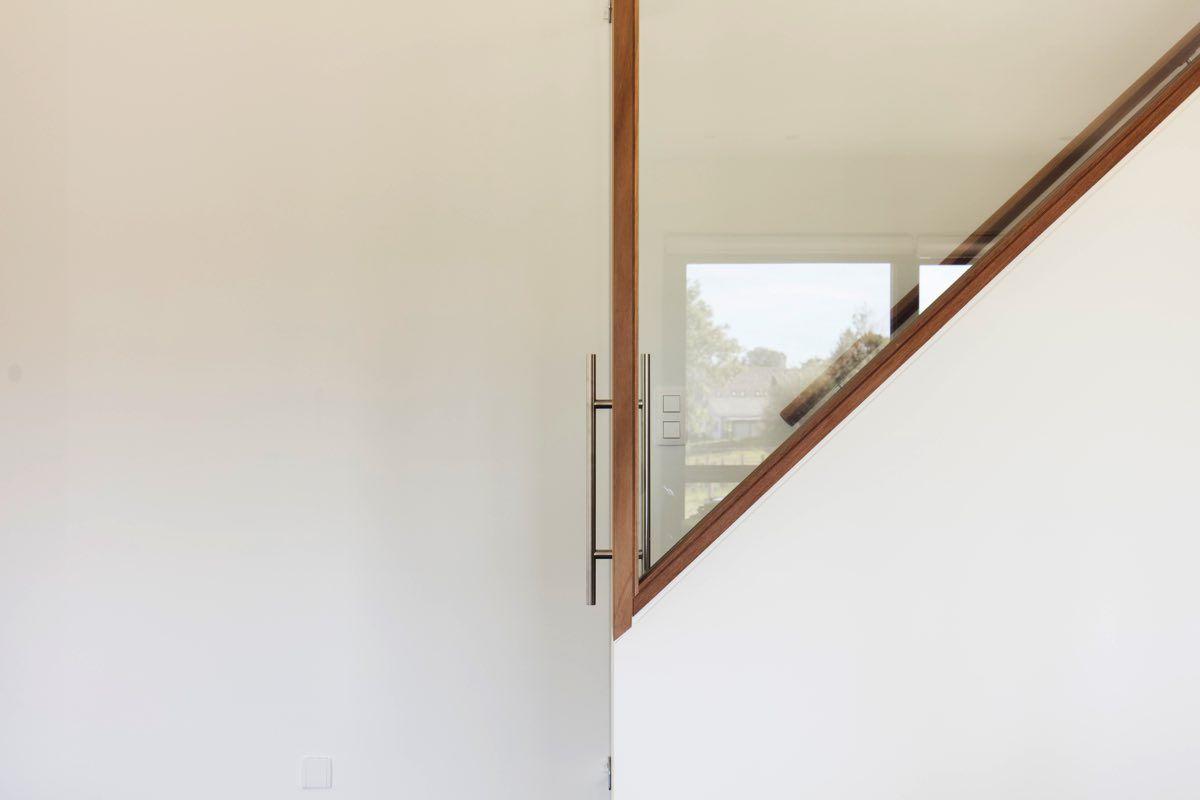 Moderne trap met glaswand en hout een realisatie van dewaele