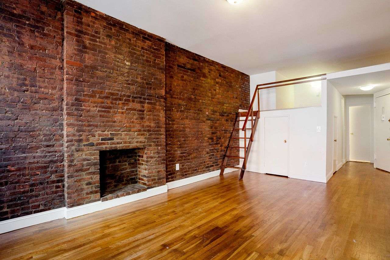 Interior of apartment. Exposed brick wall and fireplace