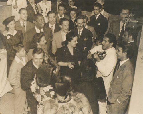 """Volta de um """"show da vitória"""" durante a 2ª Guerra mundial. Caymmi cantando e tocando violão entre artistas como: Linda Batista, Dalva de Oliveira, Assis Chateaubriand, entre outros."""