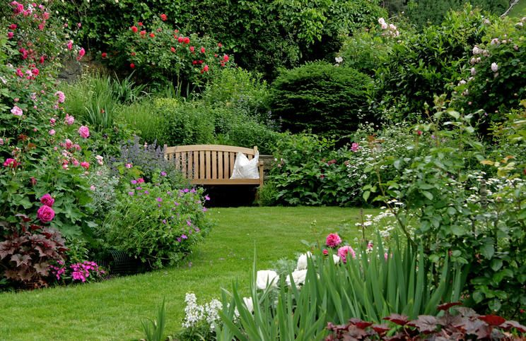 Großflächiger Blütengarten mit Sitzgelegenheit