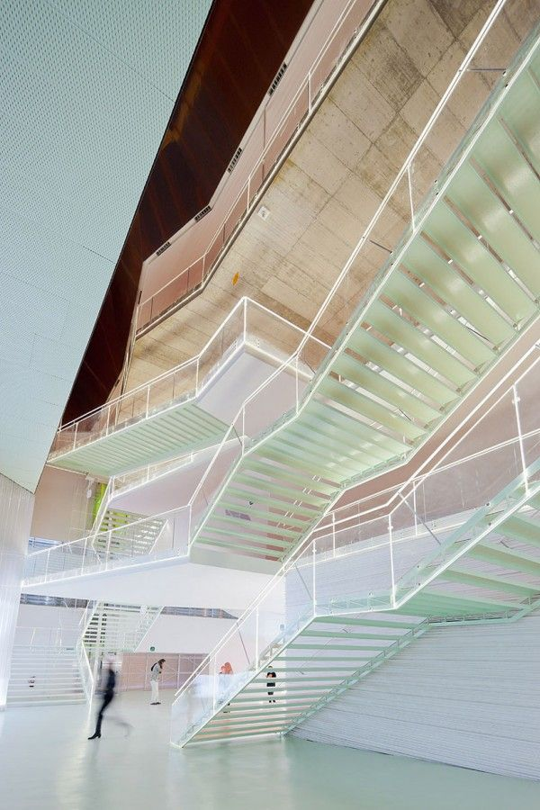 """Madrid-based architecture firm Selgascano recently completed """"el B""""; auditorium and performing center. The controversial building lines 1 kilometer of  the docks of Cartagena, Spain. With Selgascano's use of translucent materials comes a beautiful layering affect of pastel pigments that create exceptional fluidity throughout the space, captured perfectly in these photo by Iwan Baan."""