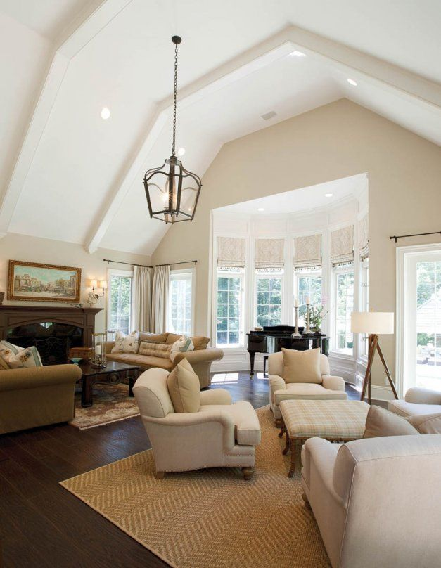 Clean White Beams Capped With Decorative Headers Accent The Elegant Lines Of The Vaulted Ceiling Vaulted Living Rooms Vaulted Ceiling Living Room Home Ceiling