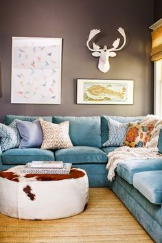 Cozy Basement Familyroom With Turquoise Velvet Sectional Sofa, Grey Walls,  Eclectic Accessories, Cowhide Ottoman   Comfy And Casual