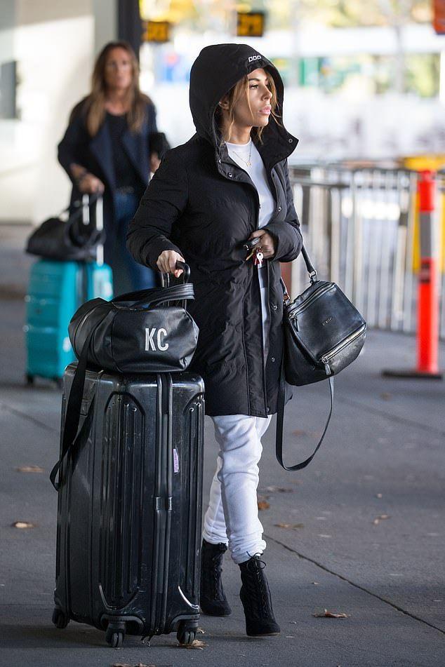 KC Osborne looks miserable as she lands back in Melbourne