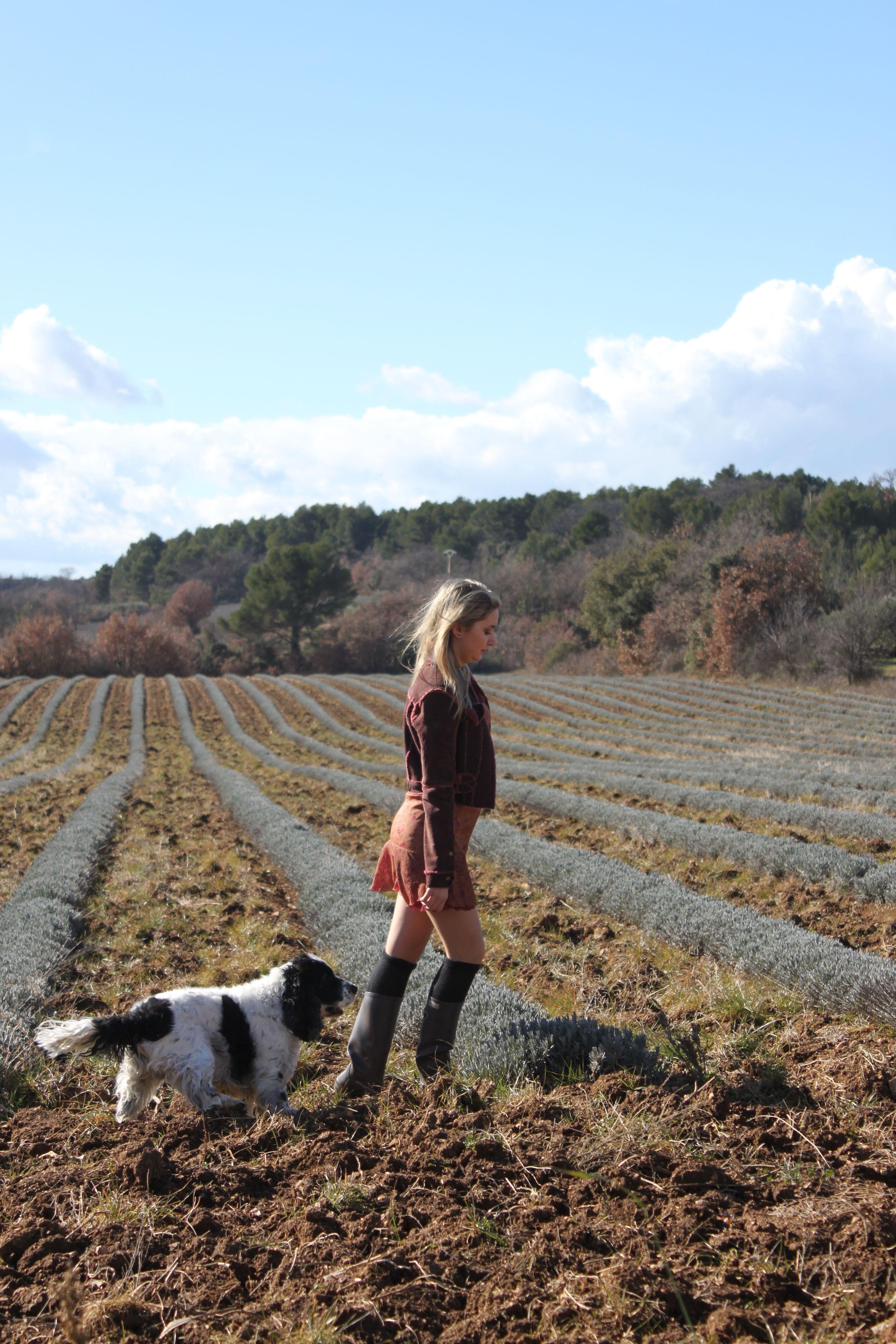 jeune femme en robe qui marche dans un champ au printemps