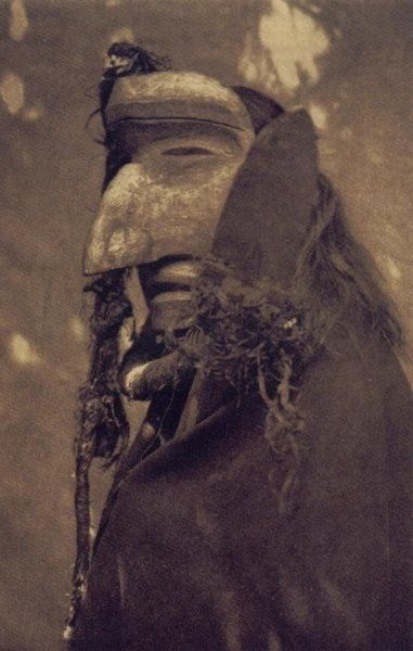 Nuhlimahla ~ Bringer of Confusion. A forest spirit of the Qagyuhl tribe of the North West Coast, British Columbia. The Nuhlimahla impersonated fools and was noted for devotion to filth and disorder. Shaman wearing ceremonial mask of the Nuhlimahla during Winter Dance Ceremony, 1914. (Edward S. Curtis, photographer 1868-1952)