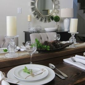 Create a rustic tablescape with a reclaimed wood plank as a runner.  Add pine cones, fresh greenery & white plates to complete the look.