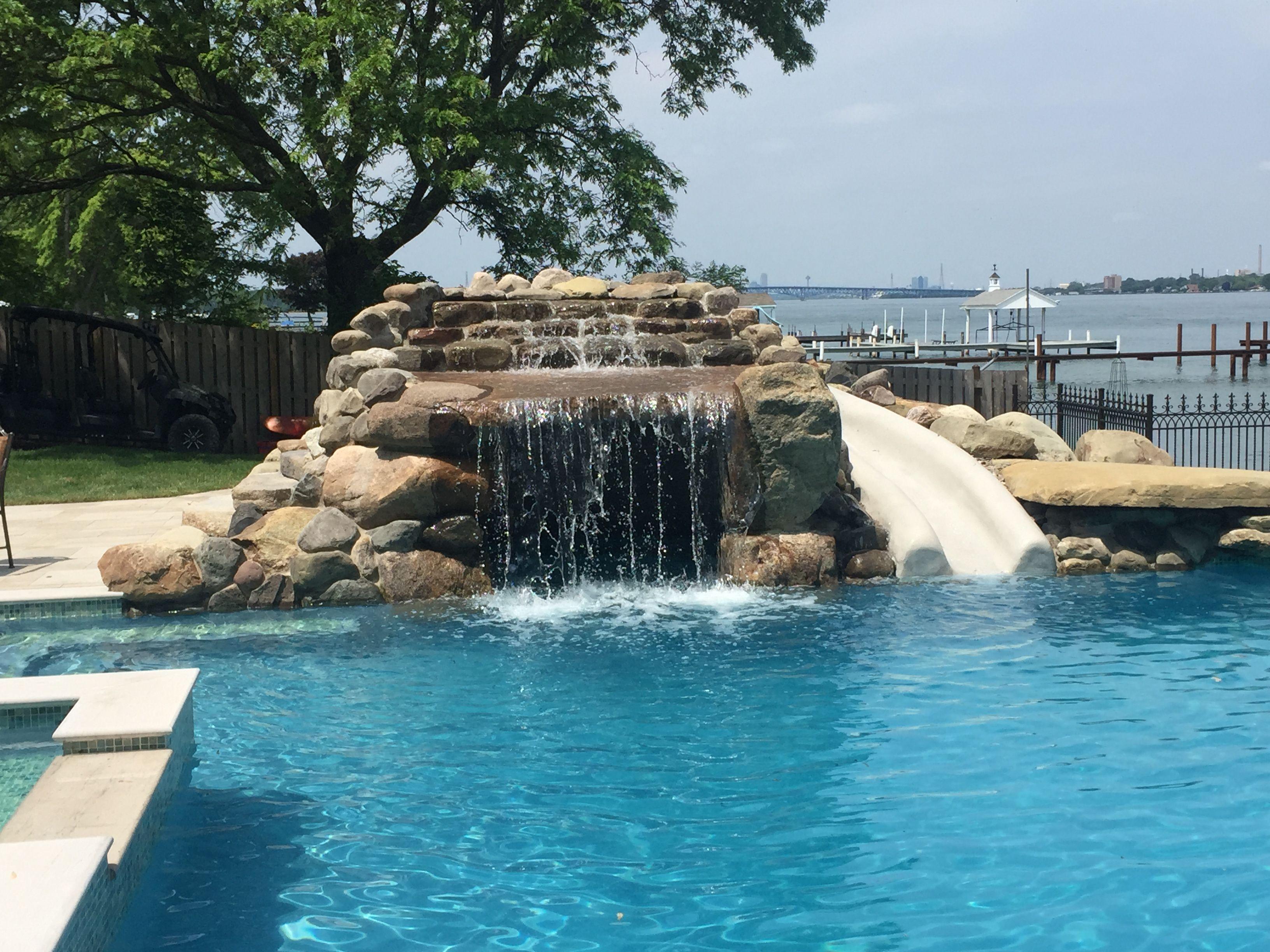 This Rectangular Pool Embraces A Negative Edge Followed By A Enjoyable Splash Pad The Pool Is Enhance Wi Pool Waterfall Rectangle Swimming Pools Backyard Pool