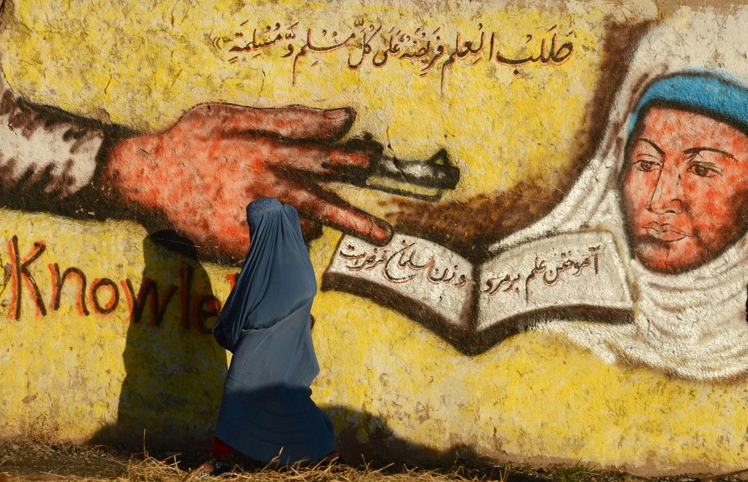 """Une femme afghane passe devant une peinture murale sur laquelle il est écrit """"La recherche du savoir est obligatoire pour chaque homme et femme musulmane"""" à Herat. Mercredi 27 janvier. #Photo: Aref Karimi pour @afpphoto  In this #photograph taken on January 27 2016 an #Afghan #woman walks past a #mural that also reads """"seeking knowledge is obligatory on every Muslim man and woman"""" in #Herat.  #photojournalism #photooftheday #bestoftheday by l_instant_parismatch"""