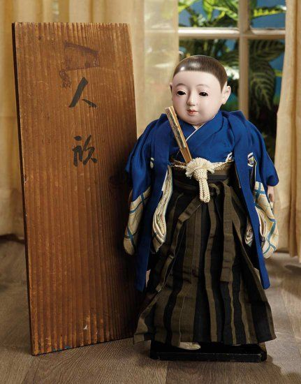 "14""-Very Fine Japanese Paper Mache Ichimatsu with Original Signature Box ....Marks: (paper label on torso, & signature on box). Comments: Japanese, circa 1920. Value Points: doll wears original royal blue inner & outer kimonos w/unusual plaid silk detail of sleeves & having five-point aristocratic crest emblems, striped crisp silk skirt, brocade obi & silk cord tie, folded fan, tabi slippers, w/elaborate label on torso, preserved in original box w/signature on lid."
