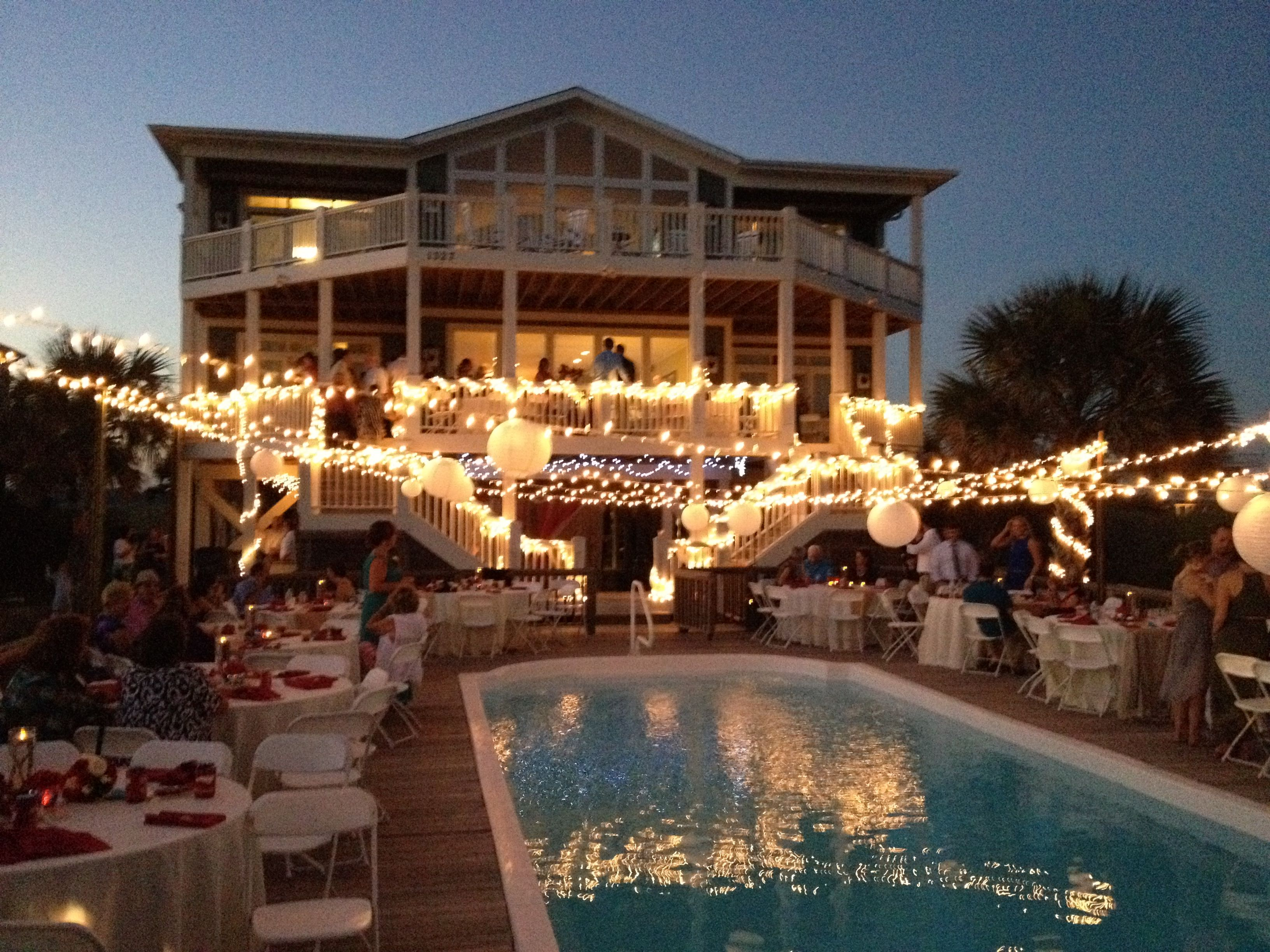 Evening Wedding Lights Across Pool Bamboo poles zip tied to pool