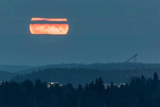 Punaisena noussut kuu valaisia lietolaisten iltaa ja hyppyrimäkeä.