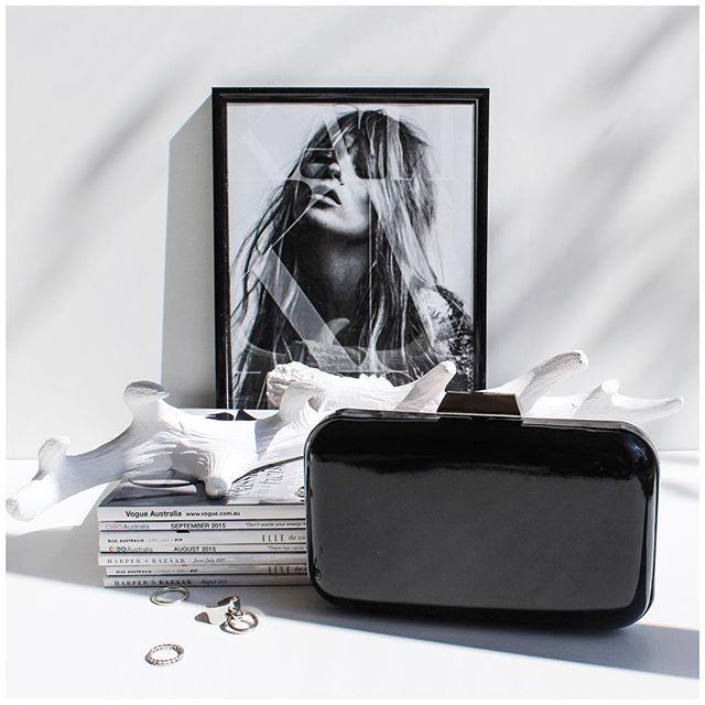 Pilha de revistas + quadro preto e branco + bolsa preta