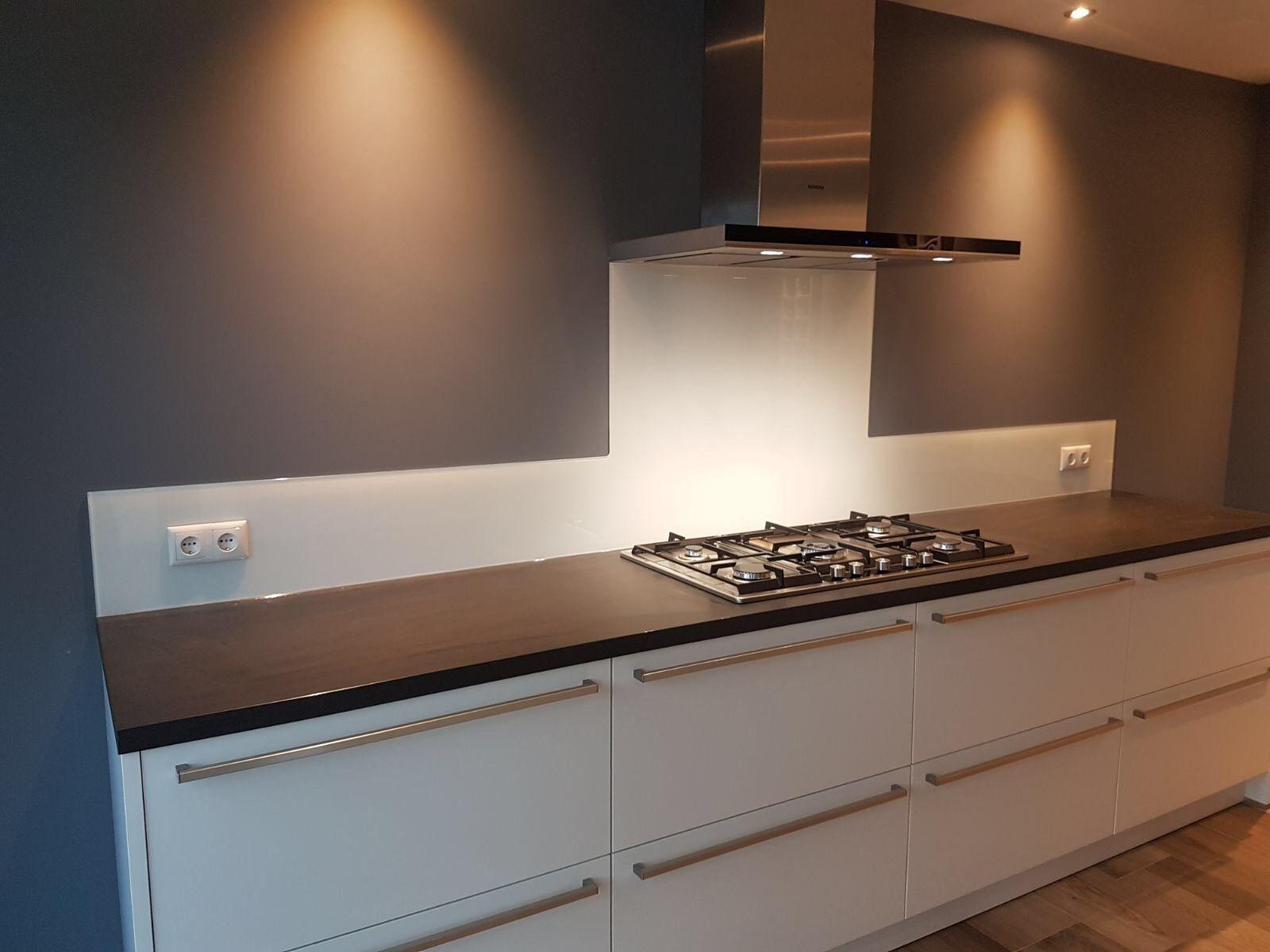 Glazen keukenwand tegen donkere muur keuken