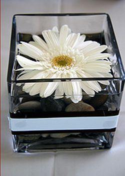 Gérbera + vaso de acrílico + fitas de cetim em preto e branco + pedras comuns.