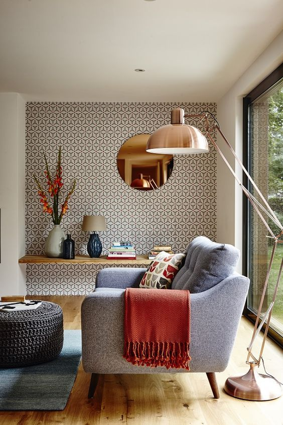 Add some geometric wallpaper to one wall in your living room to create an accent wall. For a mid-century look, choose a sofa with thin wooden legs.: