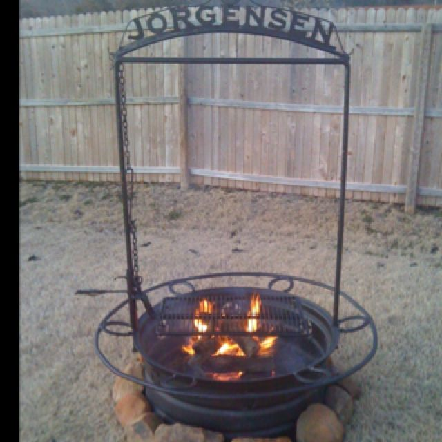 Rustic fire pit with grilling feature built from a ...