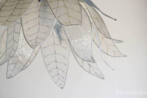 Un lampadario davvero particolare, che sfrutta la trasparenza delle foglie, dipinte a mano una per una con colore argento e oro, per creare una suggestiva atrmosfera, molto elegante.  Un lampadario che richiama la natura con le sue geometrie stilizzate, moderno, ma allo stesso tempo un po retro. misura 50 cm di diametro circa e 30 cm di altezza.  Le foglie del lampadario sono create in resina, materiale particolare per la sua leggerezza e robustezza e che dona un effetto vetro molto…