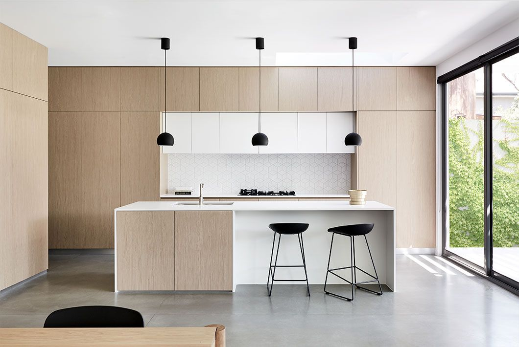 In this lovely kitchen, minimalist shelving keeps kitchen necessities liked mugs and bowls tucked away neatly but also easy to reach when they are needed.