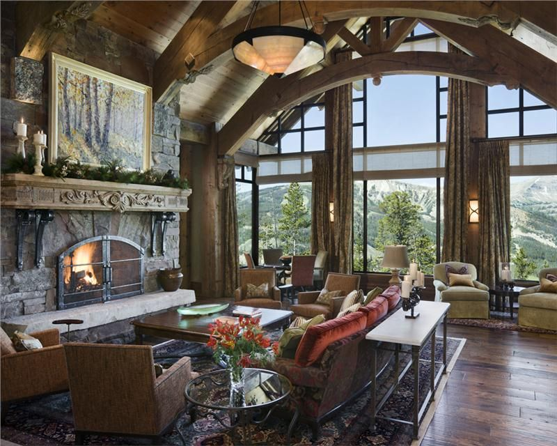 Rustic Great Room With Trusses Large Stone Fireplace And Wall Of Windows Stunning