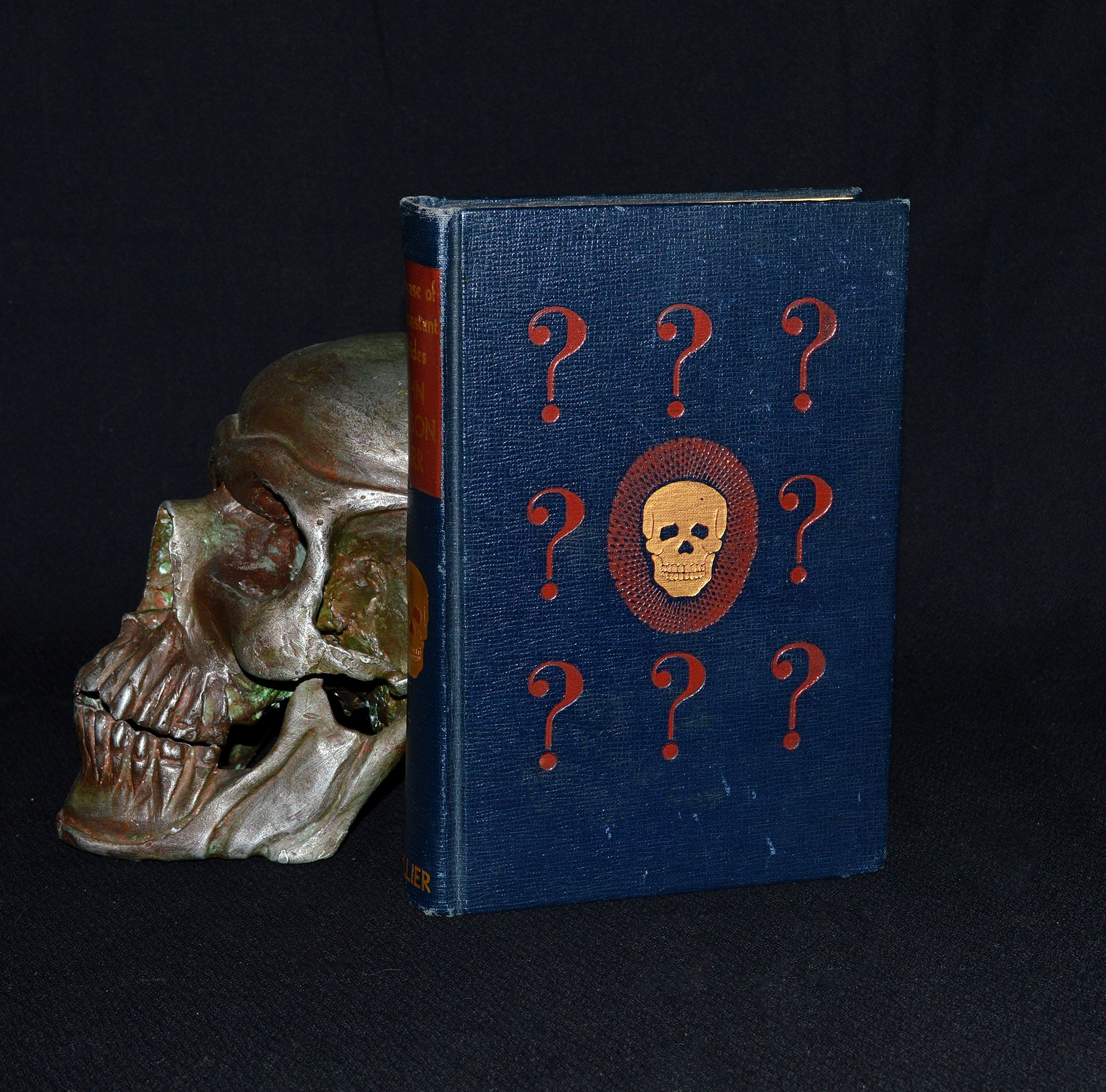 "This unusually bound book is an early 1941 edition of ""The Case of the Constant Suicides"" by John Dickinson Carr. A wonderfully obscure display piece. Carr's stories were focused on the detective / mystery / crime genres. It features unusual decorative covers with gilt skulls and blood red question marks scattered on dark blue cloth. Spine has gold titling and another golden skull with red eyes. Etsy.com/shop/CosmicLibrary"