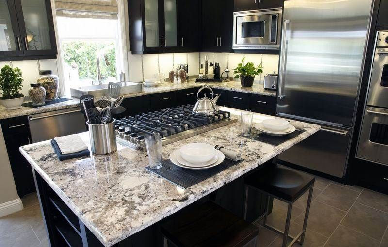 Alaskan White Granite Countertops Paired With Black Cabinets.
