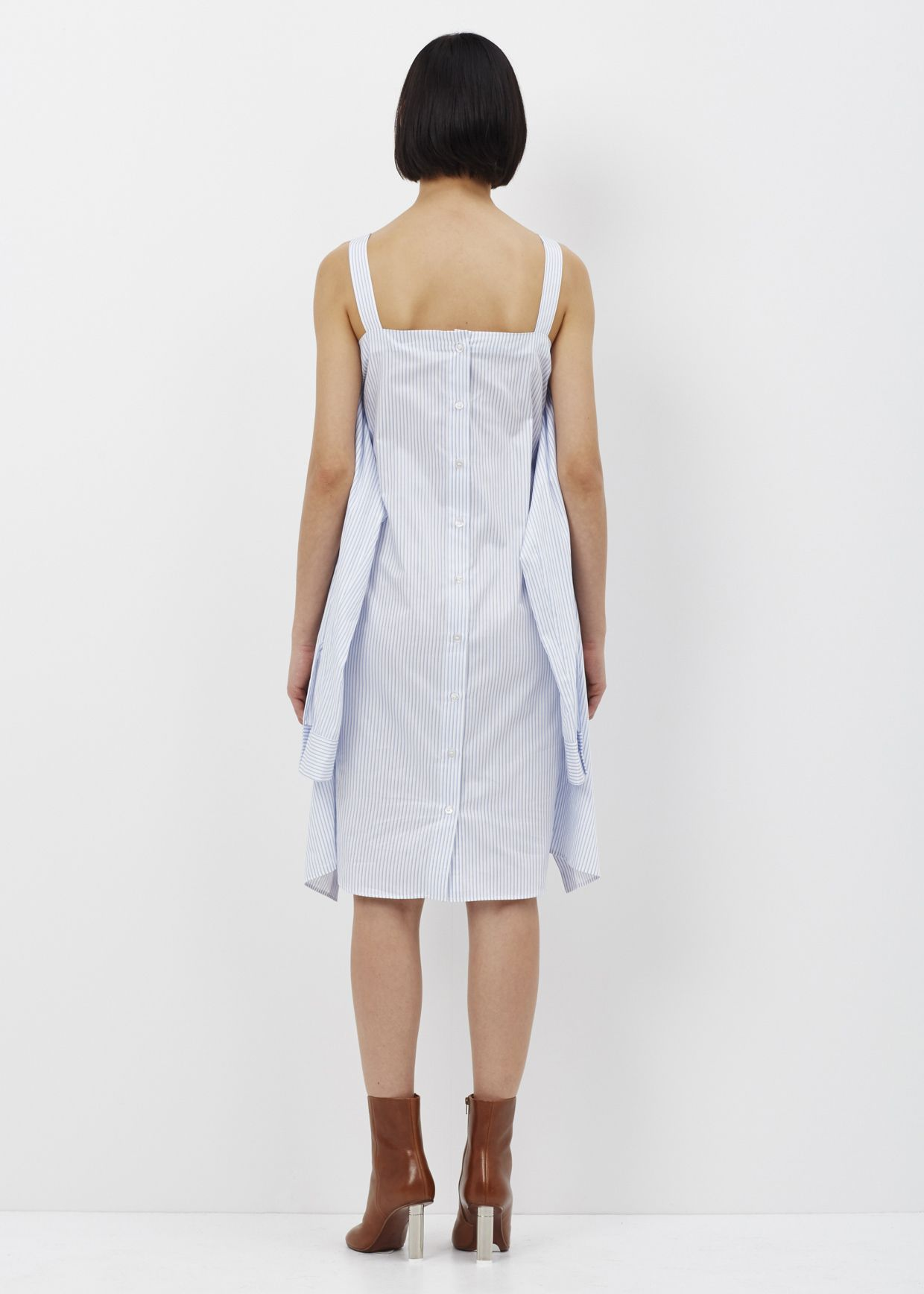 Long-bodied button down with front-shirt panel at back with shoulder strap details. Vented sleeve with button closure. Rounded body hem. Dry clean only.