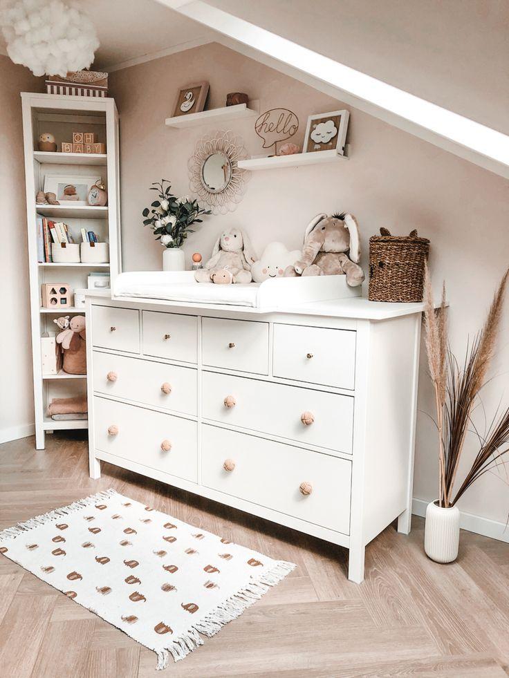 Babyzimmer Wickelkommode mit rosa Wand und hellen Holzmöbeln.