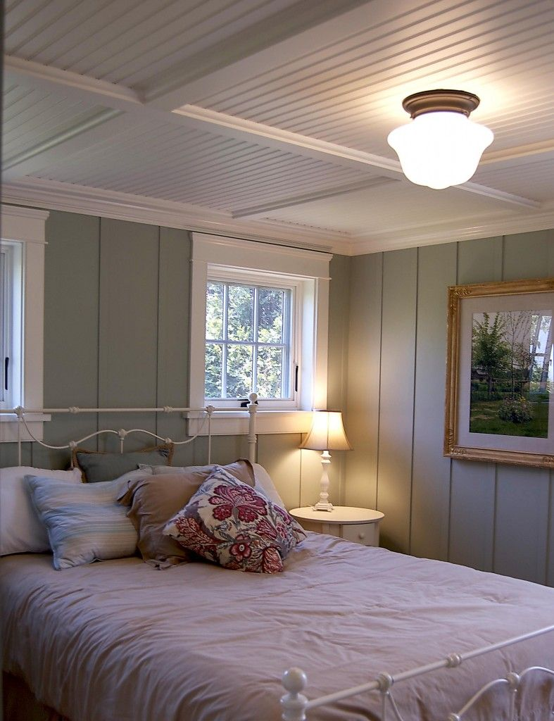 Cottage basement bedroom with floor to ceiling painted wood paneling.
