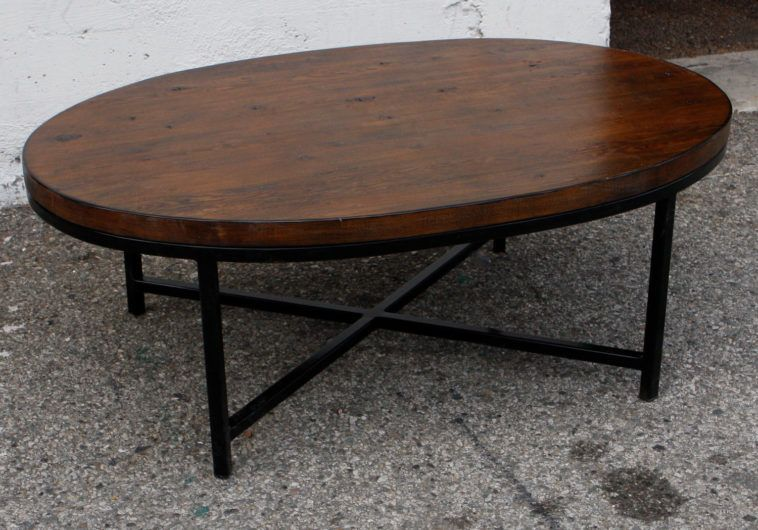 Oval Dark Brown Polished Wooden Coffee Tables With Four Black Metal Legs On Grey Floor